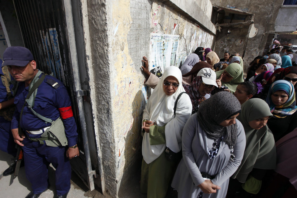 Photo -   A Navy officer stands guard as Egyptian women line up outside a polling station to cast their votes during the first day of the presidential elections in Alexandria, Egypt, Wednesday, May 23, 2012. Egyptians went to polls on Wednesday morning to elect a new president after the fall of ex-President Hosni Mubarak last year. (AP Photo/Khalil Hamra)