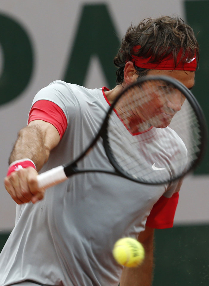 Photo - Switzerland's Roger Federer returns the ball to Argentina's Diego Sebastian Schwartzman during the second round match of  the French Open tennis tournament at the Roland Garros stadium, in Paris, France, Wednesday, May 28, 2014. Federer won 6-3, 6-4, 6-4. (AP Photo/Darko Vojinovic)