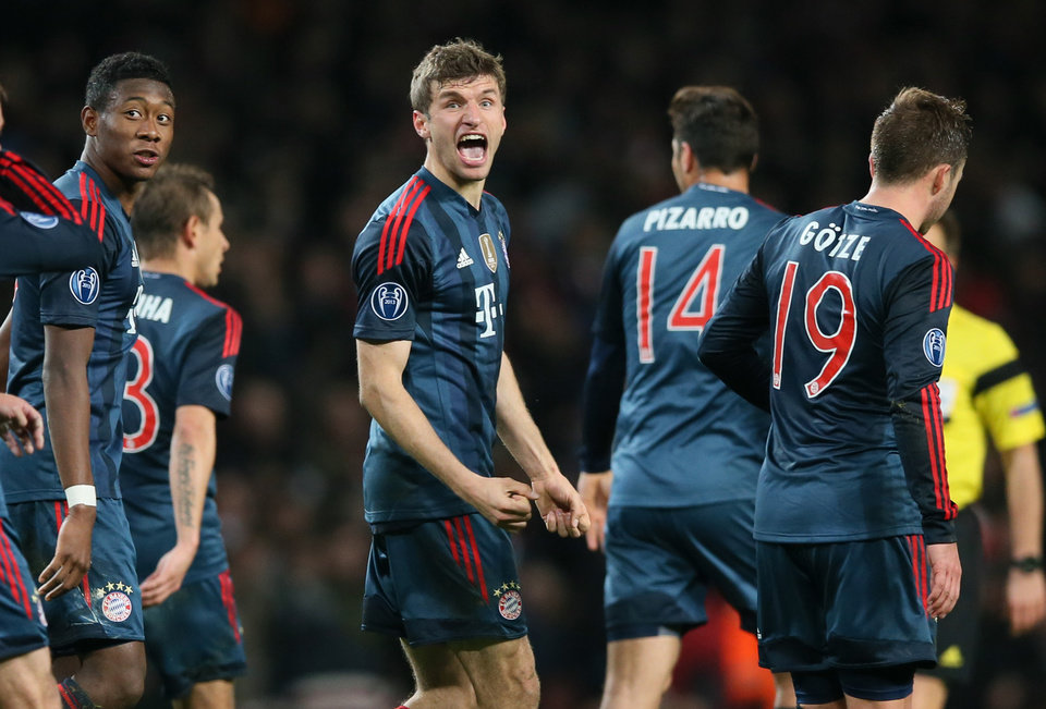 Bayern's Thomas Mueller, center, celebrates his side's second goal during a Champions League, round of 16, first leg soccer match between Arsenal and Bayern Munich at the Emirates stadium in London, Wednesday, Feb. 19, 2014 .(AP Photo/Alastair Grant)