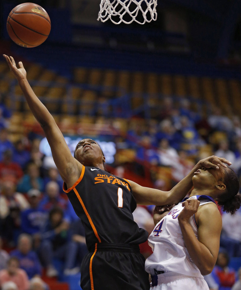 Photo - Oklahoma State guard Brittany Atkins (1) shoots while covered by Kansas guard CeCe Harper (24) during the first half of an NCAA college basketball game in Lawrence, Kan., Wednesday, Jan. 22, 2014. (AP Photo/Orlin Wagner)