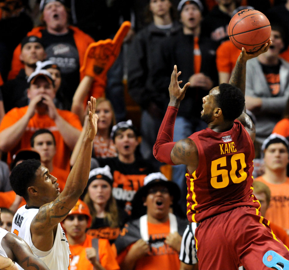 Photo - Iowa State guard DeAndre Kane, right, takes a shot over Oklahoma State Le'Bryan Nash, left, during an NCAA college basketball game in Stillwater, Okla., Monday, Feb. 3, 2014. Kane scored 26 points in the 98-97 triple overtime win over Oklahoma State. (AP Photo/Brody Schmidt)
