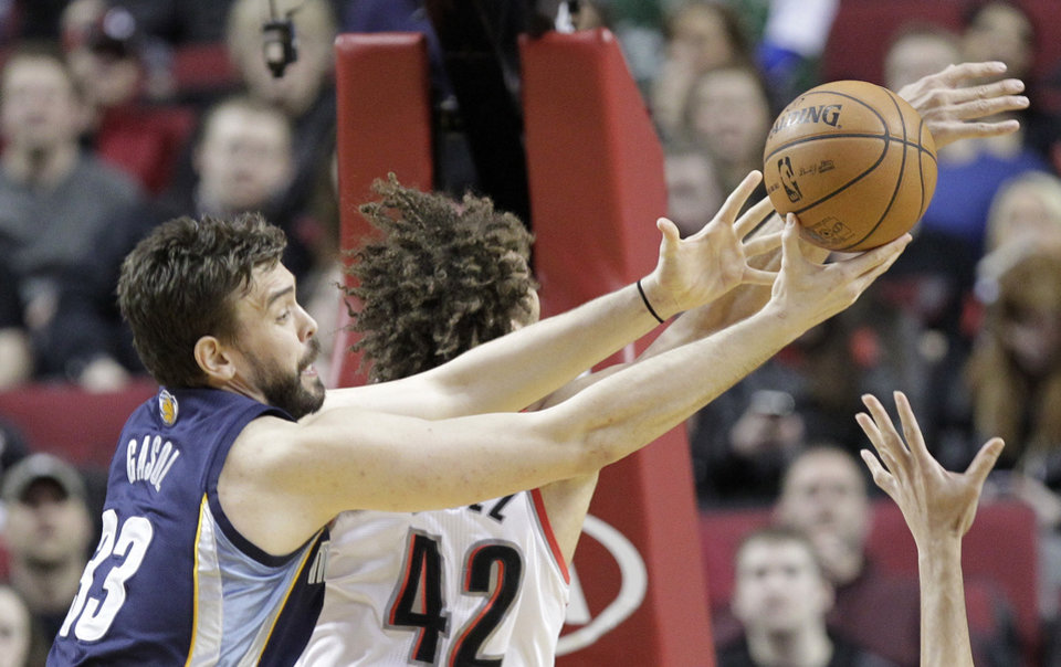 Photo - Memphis Grizzlies center Marc Gasol, left, of Spain, pulls in a rebound against Portland Trail Blazers center Robin Lopez during the first half of an NBA basketball game in Portland, Ore., Tuesday, Jan. 28, 2014. (AP Photo/Don Ryan)
