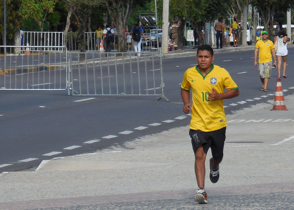 Photo - A man wearing a No. 10 Brazil soccer jersey jogs along the Rio Negro in Manaus, Brazil, Monday, June 23, 2014. There are about a dozen running groups in Manaus, in spite of the heat and humidity. (AP Photo/Chris Lehourites)