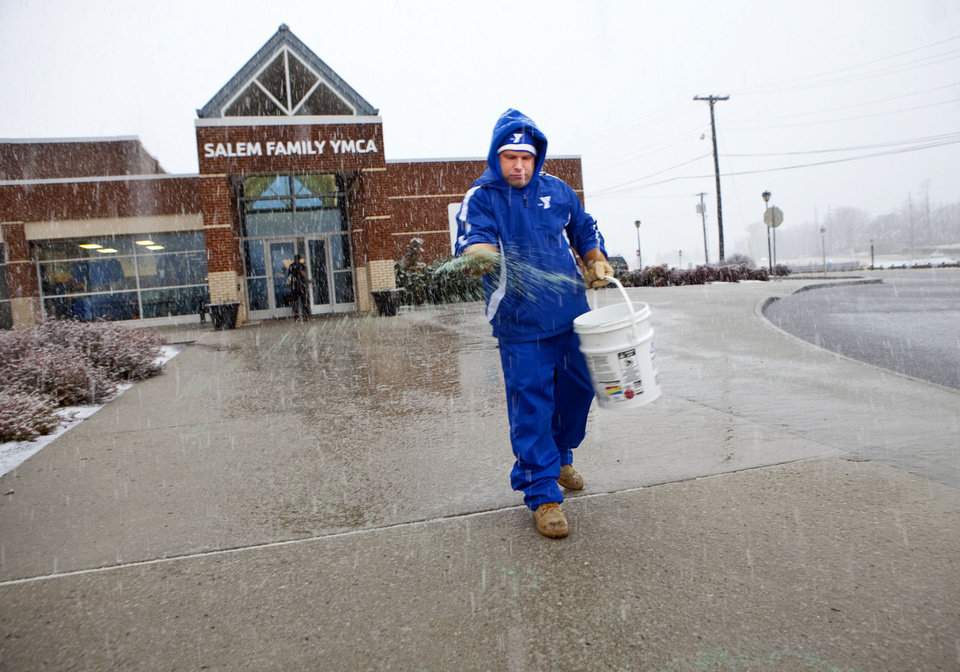 Greg Meacham, Property Director at the Salem Family YMCA on Kime Lane in Salem, Va., sprinkles salt on the sidewalk that leads to the entrance of the facility as the snow began to fall on Thursday afternoon Jan. 17, 2013. (AP PHOTO/THE ROANOKE TIMES,STEPHANIE KLEIN-DAVIS)   LOCAL TV OUT; SALEM TIMES REGISTER OUT; FINCASTLE HERALD OUT;  CHRISTIANBURG NEWS MESSENGER OUT; RADFORD NEWS JOURNAL OUT; ROANOKE STAR SENTINEL OUT