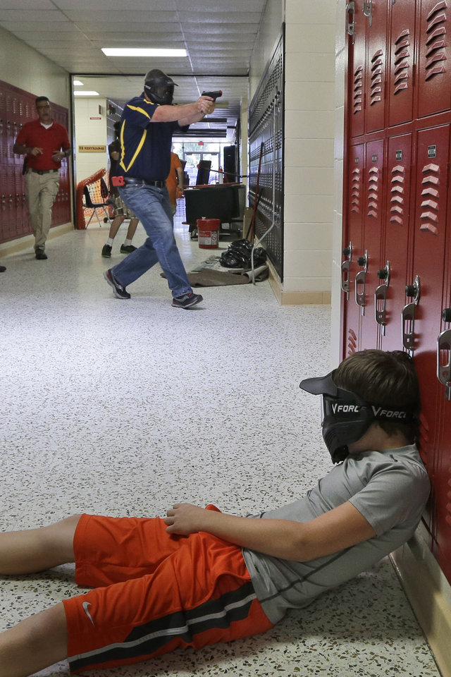Photo - In this photo taken July 11, 2013, a Clarksville schools faculty member, wearing a protective mask, rear center, carries a practice handgun toward a classroom in the city's high school in Clarksville, Ark., as students portray victims in a mock school shooting scenario. Twenty Clarksville School District staff members are training to be armed security guards on campus. (AP Photo/Danny Johnston)