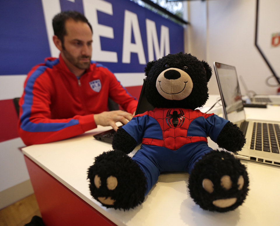 Photo - Spidey Bear sits on a table in front of U.S. Soccer's Neil Buethe at the Sao Paulo Futebol Clube, Brazil, Saturday June 28, 2014. Spidey Bear turned from his perch toward the television and sat intently and quietly (as usual) on a table some 8 feet from the big screen as Brazil took penalty kicks and salvaged its World Cup with a thrilling 3-2 win over Chile.  It has been quite an adventure tour this summer for the stuffed black bear from Iowa City belonging to the nephews of  Buethe, 6-year-old Graeme Thomas and little brother Miles, 3. (AP Photo/Julio Cortez)