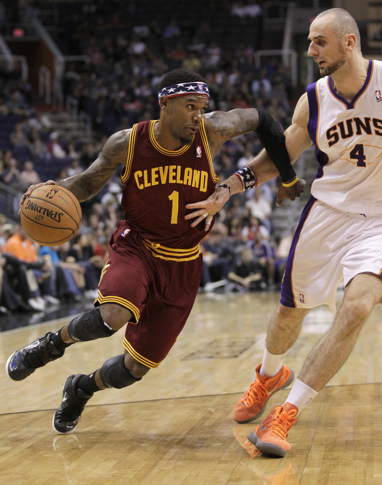 Cleveland Cavaliers' Daniel Gibson (1) drives past Phoenix Suns' Marcin Gortat (4), of Poland, during the first half of an NBA basketball game on Friday, Nov. 9, 2012, in Phoenix. (AP Photo/Matt York)