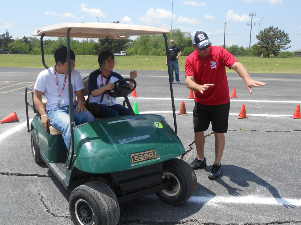 Photo - Instructor Todd Moberly works with driving students Tanner Kim and Anna Soh at Bridgestone's Teen's Drive Smart campaign, held recently at Remington Park. Photo by Kyle Fredrickson.