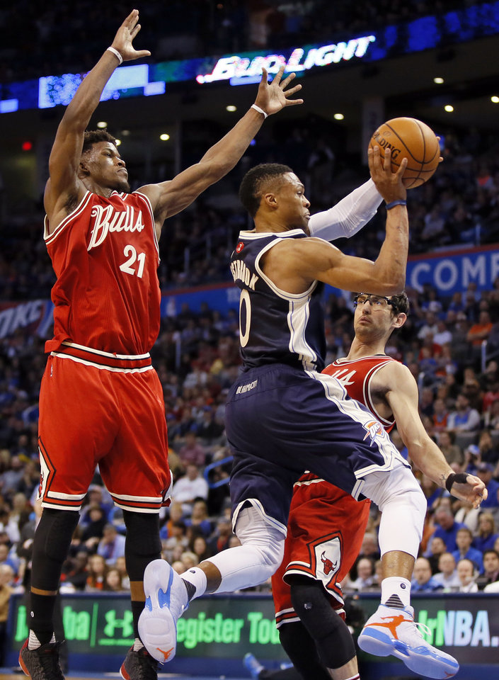 Photo - Oklahoma City's Russell Westbrook (0) passes between Chicago's Jimmy Butler (21) and Kirk Hinrich (12) during an NBA basketball game between the Oklahoma City Thunder and the Chicago Bulls at Chesapeake Energy arena in Oklahoma City, Friday, Dec. 25, 2015. Chicago won 105-96. Photo by Nate Billings, The Oklahoman