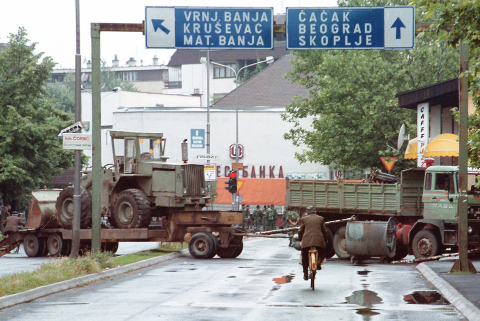 A biker rides past Yugoslav army vehicles and machinery blocking the road in downtown Kraljevo, in this 1999 photo. Kraljevo is the hometown of the Thunder's Nenad Krstic.  AP photo