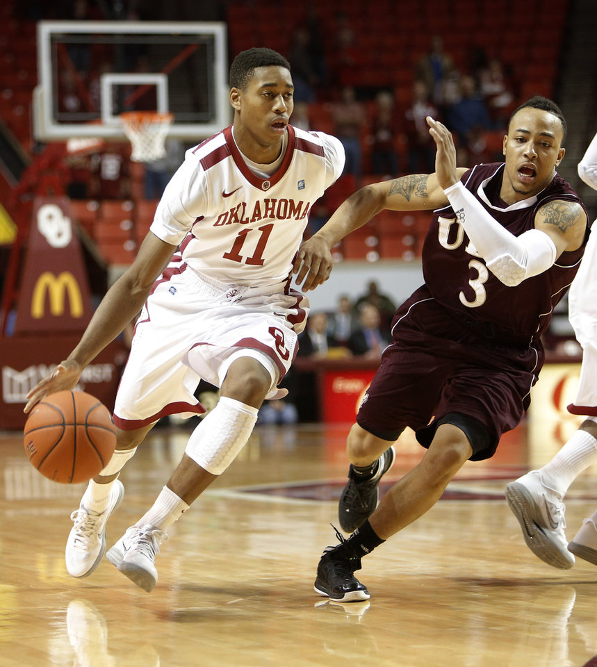 Photo - Oklahoma's Isaiah Cousins (11) drives the ball past Louisiana's Marcelis Hansberry (3) during a men's college basketball game between the University of Oklahoma and the University of Louisiana-Monroe at the Loyd Noble Center in Norman, Okla., Sunday, Nov. 11, 2012.  Photo by Garett Fisbeck, The Oklahoman