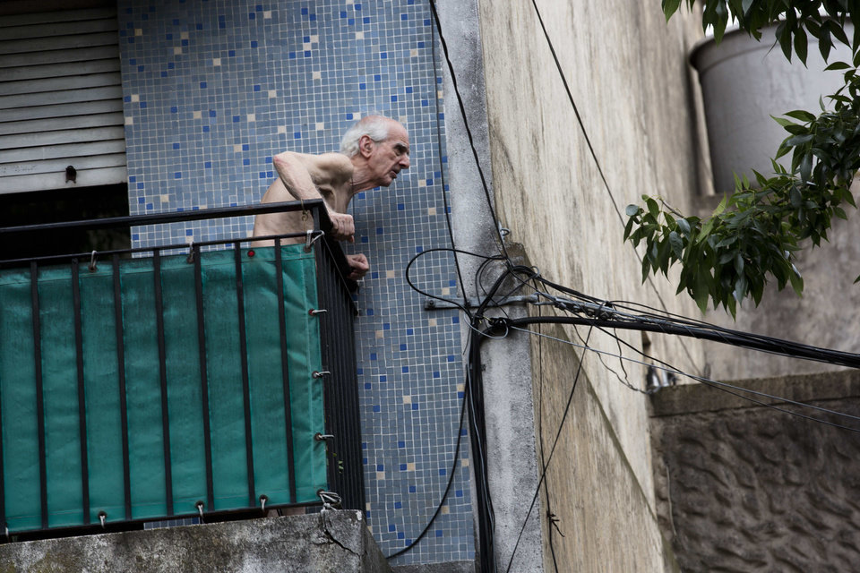 Photo - A man watches a fire from his balcony at the Iron Mountain warehouse in Buenos Aires, Argentina, Wednesday, Feb. 5, 2014. Nine first-responders were killed in the fire that destroyed an archive of bank documents, according to authorities. (AP Photo/Rodrigo Abd)