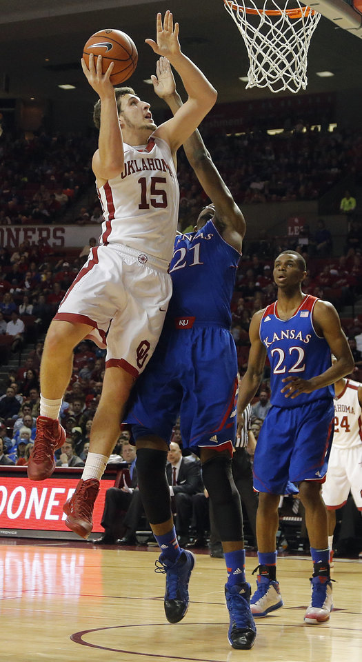 Photo - Oklahoma's Tyler Neal (15) drives to the basket over Kansas' Joel Embiid (21) during the NCAA college basketball game between the University of Oklahoma Sooners (OU) and the University of Kansas (KU) Jayhawks at Lloyd Nobel Center in Norman,  Okla. on Wednesday, Jan. 8, 2014.   .Photo by Chris Landsberger, The Oklahoman