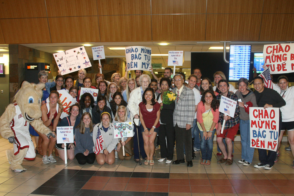 Photo - A group shot of the crowd that greeted Chinh Doan and Tu Tran as the mother and daughter arrived at Will Rogers World Airport on Monday. Photo by Ashley R. West for The Oklahoman.