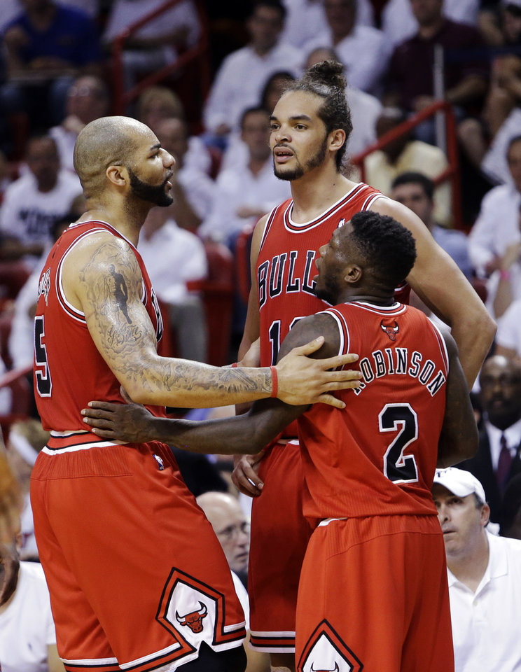 Photo - Chicago Bulls forward Carlos Boozer, left, center Joakim Noah, center, and guard Nate Robinson (2) huddle during the first half of Game 2 of their NBA basketball playoff series in the Eastern Conference semifinals against the Miami Heat, Wednesday, May 8, 2013, in Miami. (AP Photo/Lynne Sladky)
