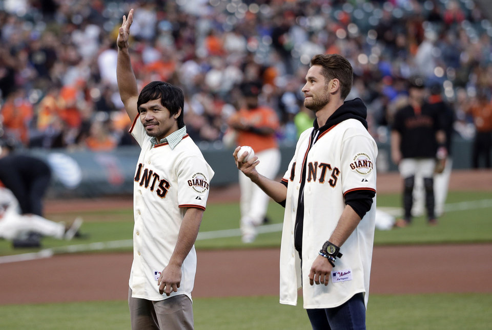 Photo - Boxers Manny Pacquiao, left, and Chris Algieri prepare to throw ceremonial first pitches during before a baseball game between the San Francisco Giants and the Milwaukee Brewers on Friday, Aug. 29, 2014, in San Francisco. (AP Photo/Marcio Jose Sanchez)