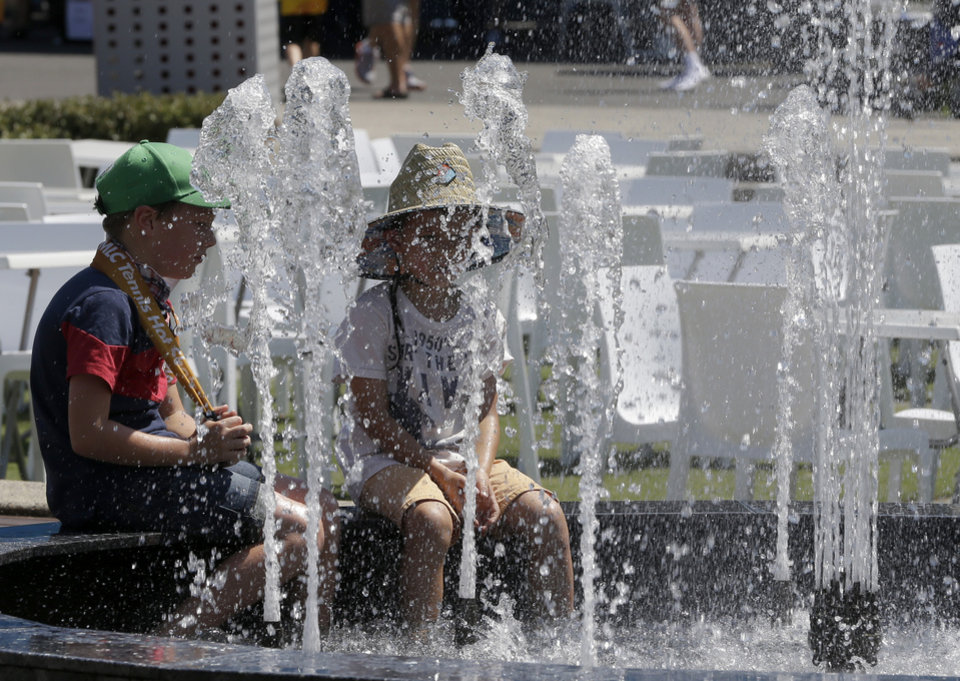 Photo - Children cool off in a fountain in Garden Square as temperatures are expected to top 44 C (112 F) during second round matches at the Australian Open tennis championship in Melbourne, Australia, Thursday, Jan. 16, 2014. (AP Photo/Mark Baker)
