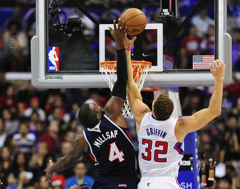 Photo - Atlanta Hawks forward Paul Millsap (4) and Los Angeles Clippers forward Blake Griffin (32) reach for a rebound in the first half of an NBA basketball game, Saturday, March 8, 2014, in Los Angeles. (AP Photo/Gus Ruelas)