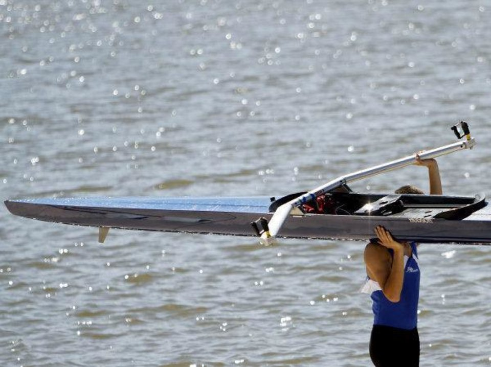 Photo - A rower carries his boat toward the Devon Boathouse after the 2011 Head of the Oklahoma Regatta Oklahoma River in Oklahoma City on Sunday, October 2, 2011. Photo by John Clanton, The Oklahoman ORG XMIT: KOD  JOHN CLANTON - John Clanton