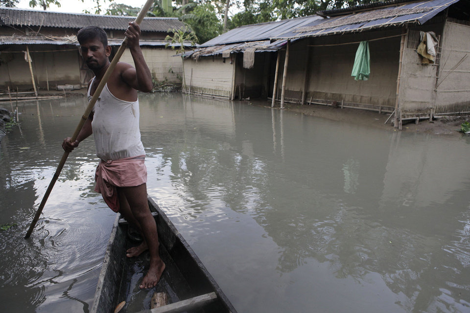 Photo -   A man rows a boat through flood waters at Himoluwa about 75 kilometers (47 miles) west of Gauhati, India, Sunday, July 1, 2012. More than a week of heavy rains in Assam state have caused the massive Brahmaputra River, one of Asia's largest to exceed danger levels. Smaller rivers have also overflowed their banks.(AP Photo/Anupam Nath)