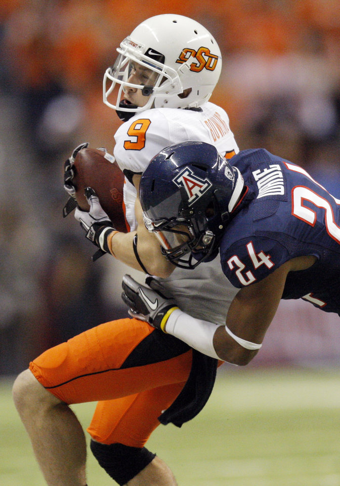 Photo - OSU's Bo Bowling (9) is stopped by Trevin Wade (24) of Arizona during the Valero Alamo Bowl college football game between the Oklahoma State University Cowboys (OSU) and the University of Arizona Wildcats at the Alamodome in San Antonio, Texas, Wednesday, December 29, 2010. Photo by Nate Billings, The Oklahoman