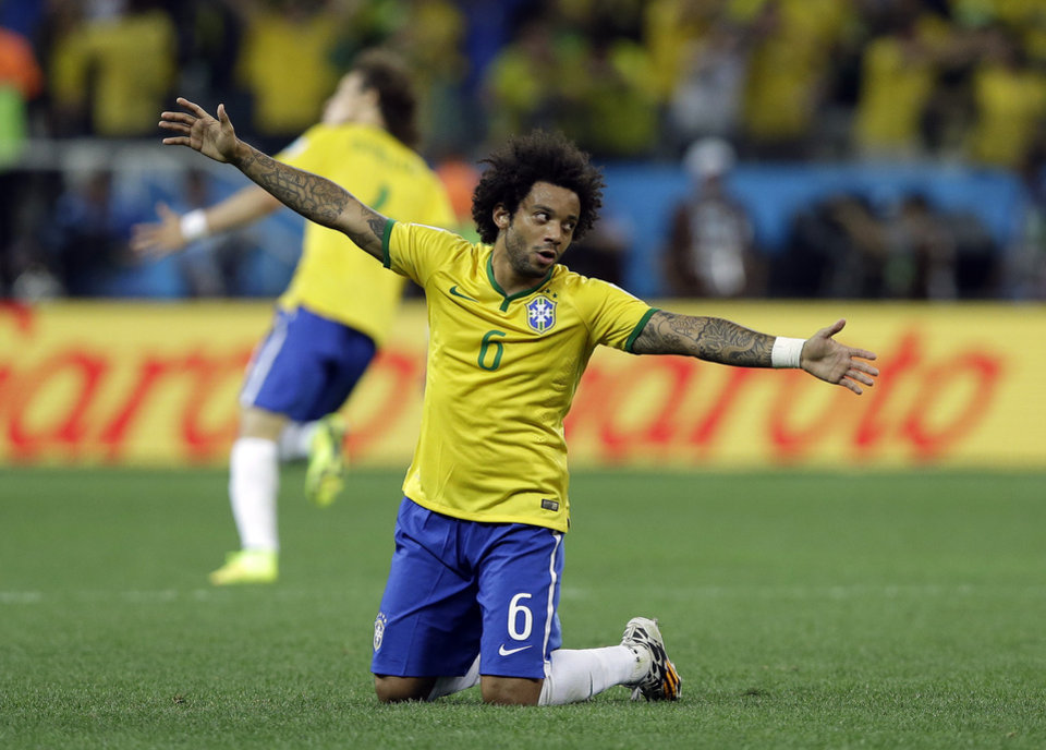 Photo - Brazil's Marcelo celebrates after  Oscar scored the 3rd goal during the group A World Cup soccer match between Brazil and Croatia, the opening game of the tournament, in the Itaquerao Stadium in Sao Paulo, Brazil, Thursday, June 12, 2014.(AP Photo/Kirsty Wigglesworth)