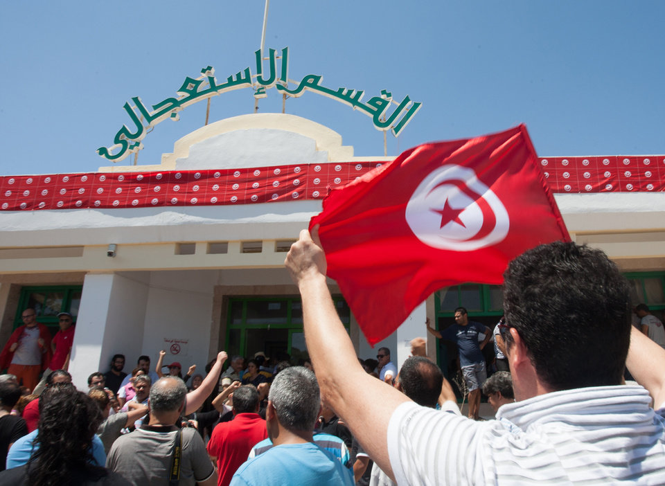 Photo - Supporters of the Popular Front party gather at Mahmoud Materi hospital, north of Tunis, in support of Mohammed Brahmi who was shot to death in his car outside his home, in Tunisia, Thursday, July 25, 2013. Brahmi, 58, of an Arab nationalist political party was in his car outside home when gunmen fired several shots at him, said Interior Ministry spokesman Mohammed Ali Aroui. It is the second killing of an opposition member this year, following that of Chokri Belaid, a member of the same leftist Popular Front coalition as Brahmi. Belaid was also shot dead in his car outside his home in February. His killing provoked a political crisis that nearly derailed Tunisia's political transition. (AP Photo/Amine Landoulsi)