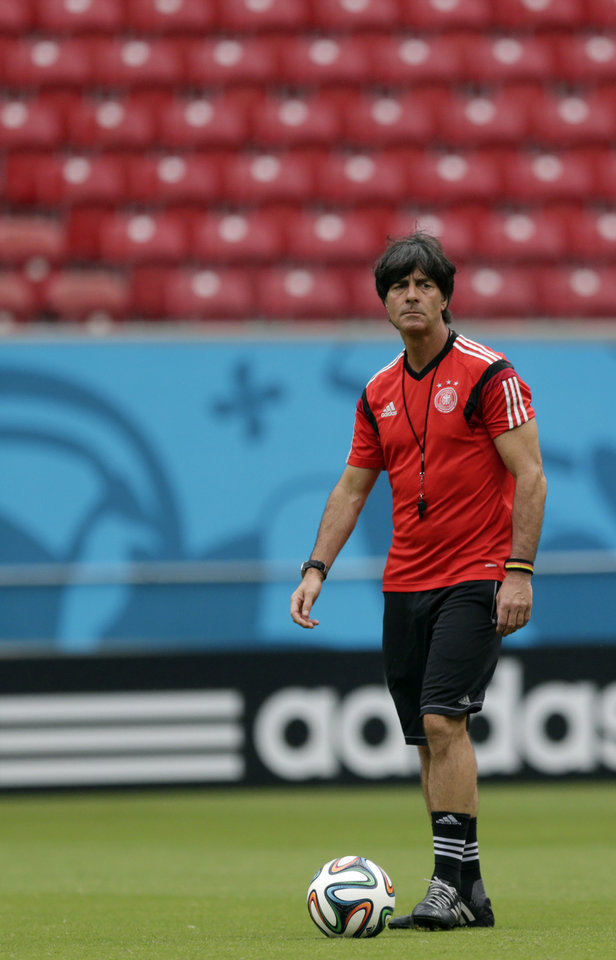Photo - Germany's head coach Joachim Loew walks the pitch with a ball during a training session in Recife, Brazil, Wednesday, June 25, 2014. Germany will play the United States in group G of the 2014 soccer World Cup on June 26. (AP Photo/Julio Cortez)