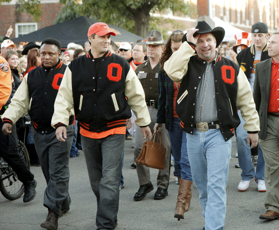 Photo - Barry Sanders, Robin Ventura and Garth Brooks wave to the crowd during the walk to the stadium before the college football game between Oklahoma State University (OSU) and the University of Missouri (MU) at Boone Pickens Stadium in Stillwater, Okla. Saturday, Oct. 17, 2009.  Photo by Doug Hoke, The Oklahoman