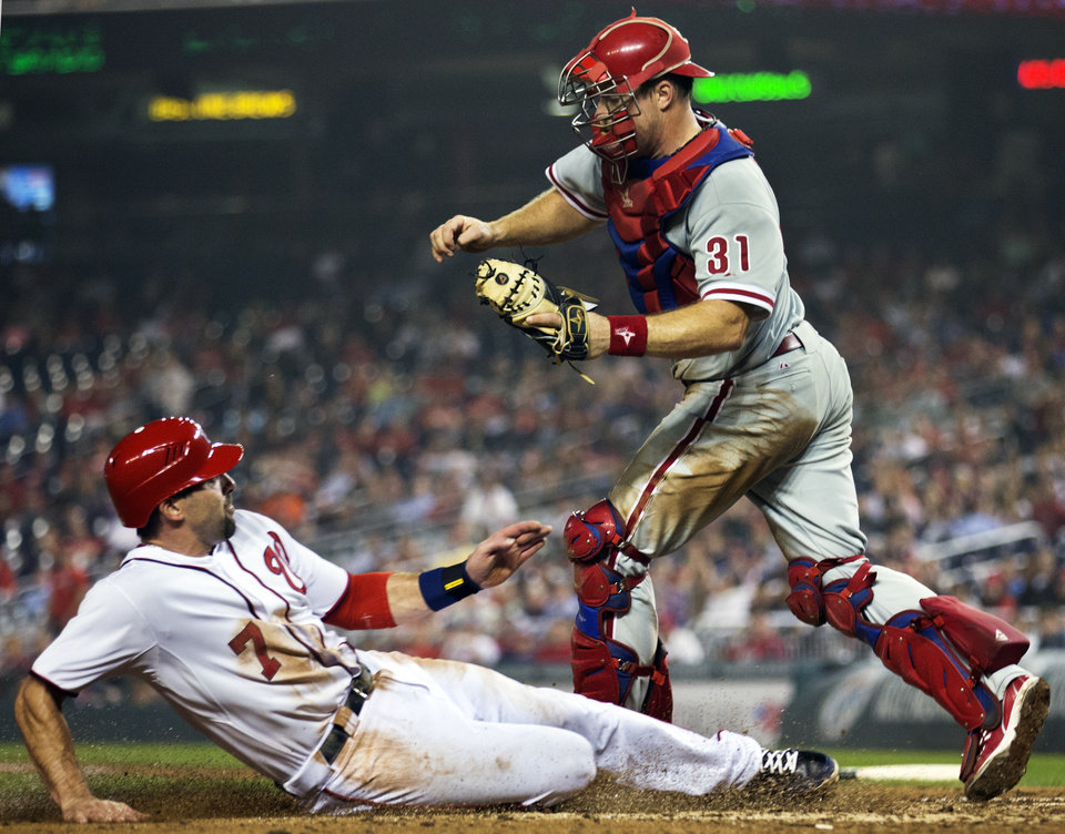 Photo -   Philadelphia Phillies catcher Erik Kratz (31) evades the slide by Washington Nationals' Mark DeRosa (7) as DeRosa is forced out at home during the eighth inning of a baseball game in Washington, Tuesday, Oct. 2, 2012. The Nationals won 4-2. (AP Photo/Manuel Balce Ceneta)