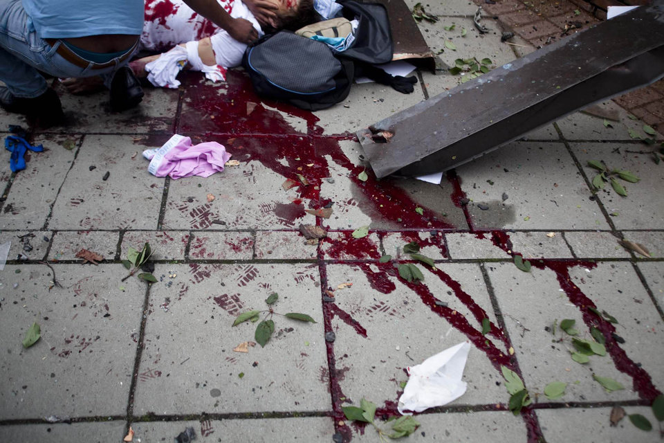 Blood smears the pavement, as a victim is treated outside government buildings in the centre of Oslo, Friday July 22, 2011, following an explosion that tore open several buildings including the prime minister's office, shattering windows and covering the street with documents.(AP Photo/Fartein Rudjord) NORWAY OUT: ORG XMIT: LON861