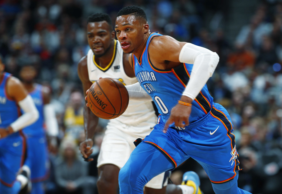 Photo - Oklahoma City Thunder guard Russell Westbrook, front, picks up a loose all in front of Denver Nuggets forward Paul Millsap during the first half of an NBA basketball game Thursday, Nov. 9, 2017, in Denver. (AP Photo/David Zalubowski)
