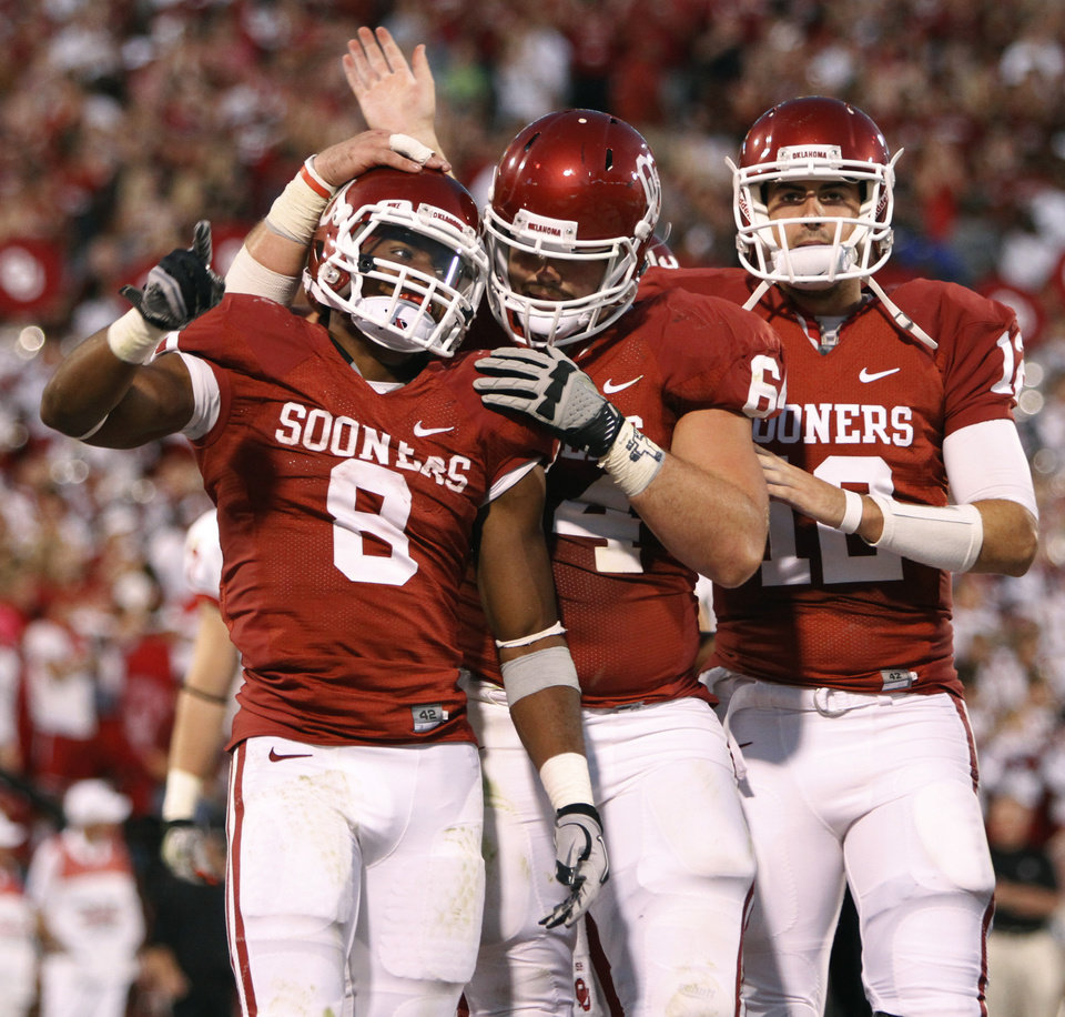 Oklahoma's Dominique Whaley (8), Gabe Ikard (64), and Landry Jones (12) celebrate after a touchdown during the college football game between the University of Oklahoma Sooners (OU) and the Ball State Cardinals at Gaylord Family-Memorial Stadium on Saturday, Oct. 01, 2011, in Norman, Okla. Photo by Bryan Terry, The Oklahoman