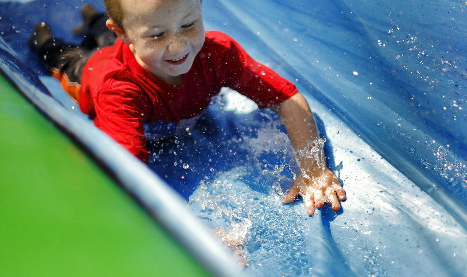 Photo - Bladen Russell, 5, cools off as he slides through the water on the water slide during the Yukon Freedom Fest at the Yukon City Park on Thursday , July 4, 2013, in Yukon, Okla. Photo by Chris Landsberger, The Oklahoman