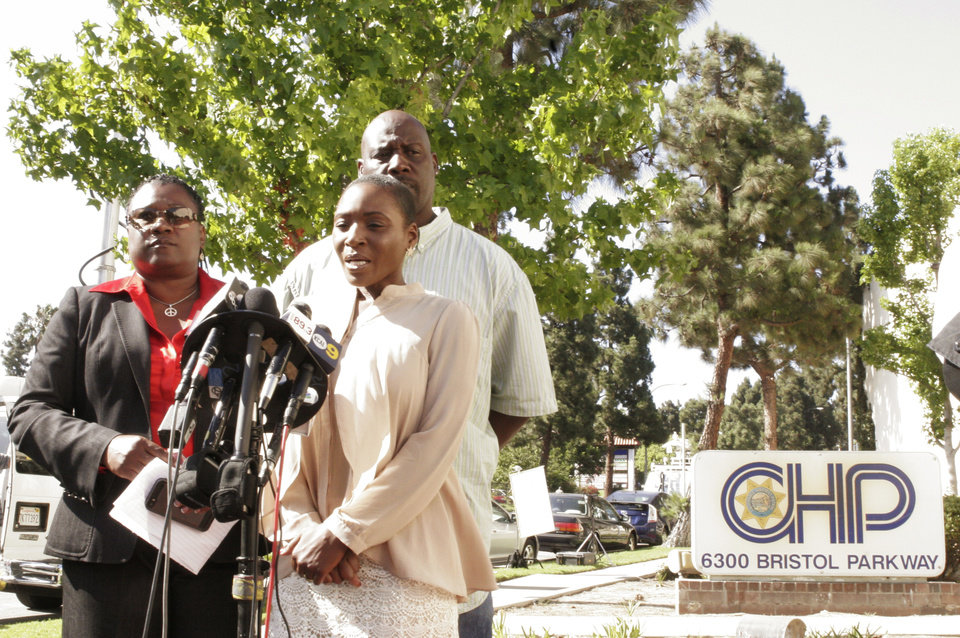 Photo - Attorney Caree Harper, far left, Robert Nobles who is husband to Maisha Allums, daughter of Marlene Pinnock who was seen on the videotape being repeatedly punched, take questions from the media outside the CHP offices in Culver City, Calif., Tuesday, July 8, 2014.  An earlier video provided by motorist David Diaz, shows  California Highway Patrol officer straddling a woman while punching her in the head on the shoulder of a Los Angeles freeway. The woman, identified as Marlene Pinnock, had been walking on Interstate 10 west of downtown Los Angeles, endangering herself and people in traffic, and the officer was trying to restrain her, according to a CHP assistant chief. The officer, who has not been identified, has been placed on administrative leave during an investigation. (AP Photo/Tami Abdollah)