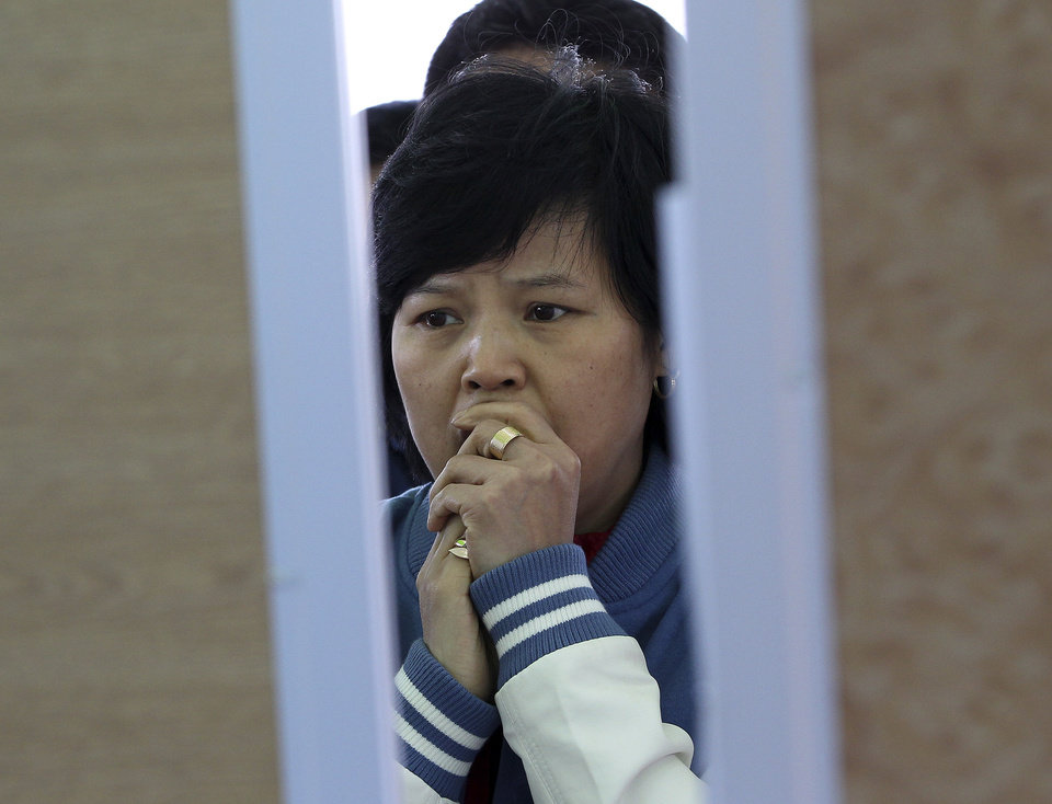 Photo - A relative of a passenger aboard the sunken ferry Sewol in the water off the southern coast watches the official list of the dead victims at a port in Jindo, South Korea, Monday, April 21, 2014. Divers continued the grim work of recovering bodies from inside the sunken South Korean ferry Monday, as a newly released transcript showed the ship was crippled by confusion and indecision well after it began listing. The transcript suggests that the chaos may have added to a death toll that could eventually exceed 300. (AP Photo/Ahn Young-joon)