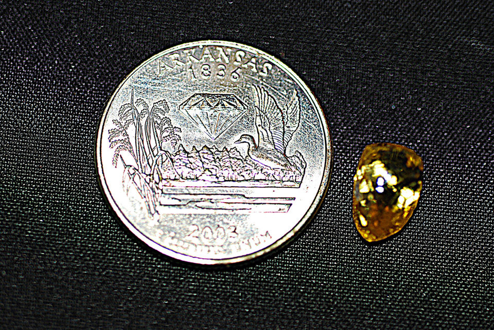 The God's Gem diamond, found Saturday at Crater of Diamonds State Park in Arkansas by 14-year-old Tana Clymer, of Oklahoma City, sits next to a U.S. quarter. The 3.8-carat canary diamond is gem quality and could be worth thousands of dollars. Photo provided by Crater of Diamonds State Park <strong></strong>