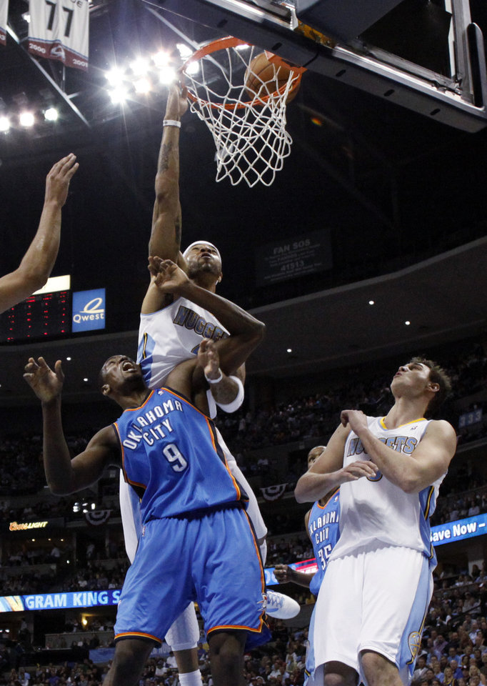 Photo - Denver Nuggets forward Kenyon Martin (4) goes up for a shot against Oklahoma City Thunder forward Serge Ibaka (9) from the Republic of Congo as Denver Nuggets forward Danilo Gallinari (8) from Italy looks on during the second half in game 4 of a first-round NBA basketball playoff series Monday, April 25, 2011, in Denver. (AP Photo/Jack Dempsey)