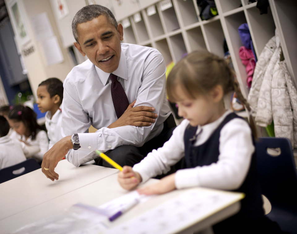 Photo - President Barack Obama sits with Emily Hare as she completes her spelling lessons during his visit to a preschool classroom at Powell Elementary School in the Petworth neighborhood of Washington, Tuesday, March 4, 2014. Obama visited the school to talk about his 2015 budget proposal, which was released today. Powell elementary has seen rapid growth in recent years and serves a predominantly Hispanic student body. Washington DC Mayor Vincent Gray, who greeted Obama at the school, recently directed $20 million to Powell for a planned modernization and addition. (AP Photo/Pablo Martinez Monsivais)