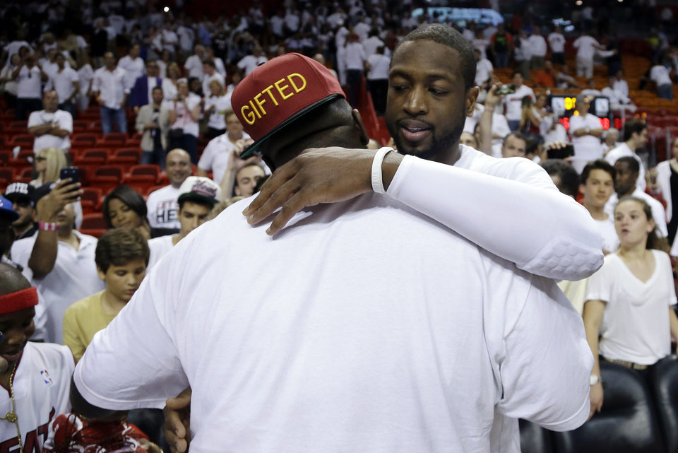 Photo - Miami Heat's Dwyane Wade, right, hugs rapper Rick Ross, left, following Game 2 of their NBA basketball playoff series in the Eastern Conference semifinals against the Chicago Bulls, Wednesday, May 8, 2013, in Miami. The Heat won 115-78. (AP Photo/Lynne Sladky)