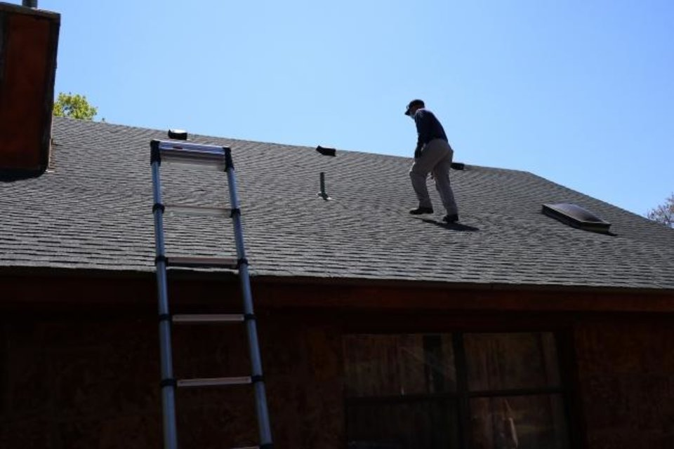 Photo -  Cord Werner, of A to Z Inspections, checks the roof at 14501 Turkey Hills Road in Newalla.  [DOUG HOKE/THE OKLAHOMAN]