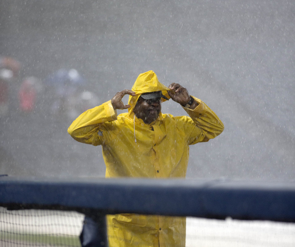 Photo - An Atlanta Braves security guard covers up in during a rain delay at a baseball game between the Braves and the Washington Nationals on Saturday, Aug. 9, 2014 in Atlanta. (AP Photo/John Bazemore)