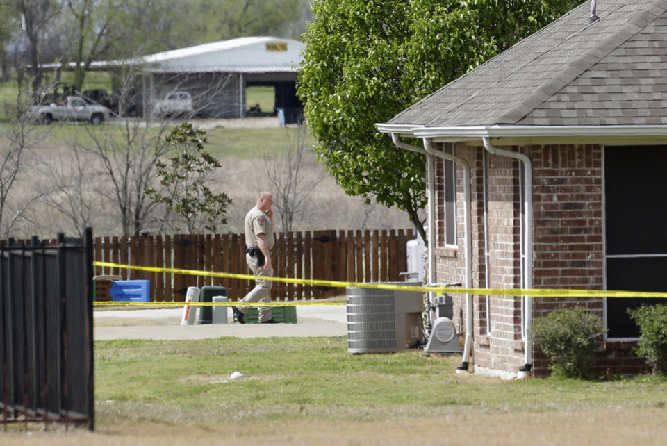 Photo - A Kaufman County Sheriff's deputy walks near the taped-off property of Kaufman County District Attorney Mike McLelland, near Forney, Texas, on Sunday, March 31, 2013. On Saturday, McLelland and his wife, Cynthia, were murdered in their home. (AP Photo/Mike Fuentes)