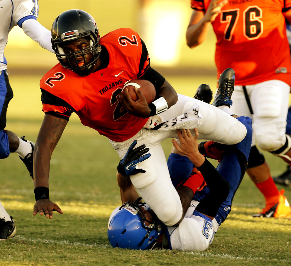 Photo - Douglass' Deondre Clark is brought down by  Southeast High School's Kyle Wooldridge at the All City Football Preview at Douglass High School on Friday, Aug. 30, 2013 in Oklahoma City, Okla.  Photo by Steve Sisney, The Oklahoman
