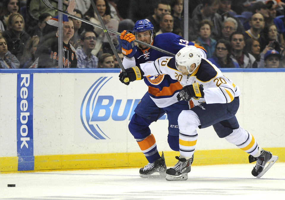 Photo - Buffalo Sabres' Henrik Tallinder (20) crashes into New York Islanders' Colin McDonald (13) to chase the puck in the second period of an NHL hockey game on Saturday, March 15, 2014, in Uniondale, N.Y. (AP Photo/Kathy Kmonicek)