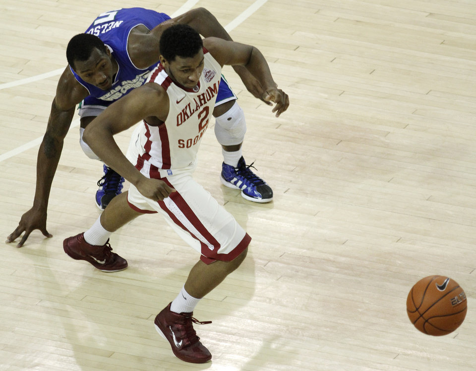 Photo - OU: Oklahoma's Steven Pledger (2) and Texas A&M's Will Nelson (5) fight for a ball during a college basketball game between the University of Oklahoma and Texas A&M Corpus Christi at McCasland Field House in Norman, Okla., Monday, Dec. 31, 2012.  Photo by Garett Fisbeck, For The Oklahoman