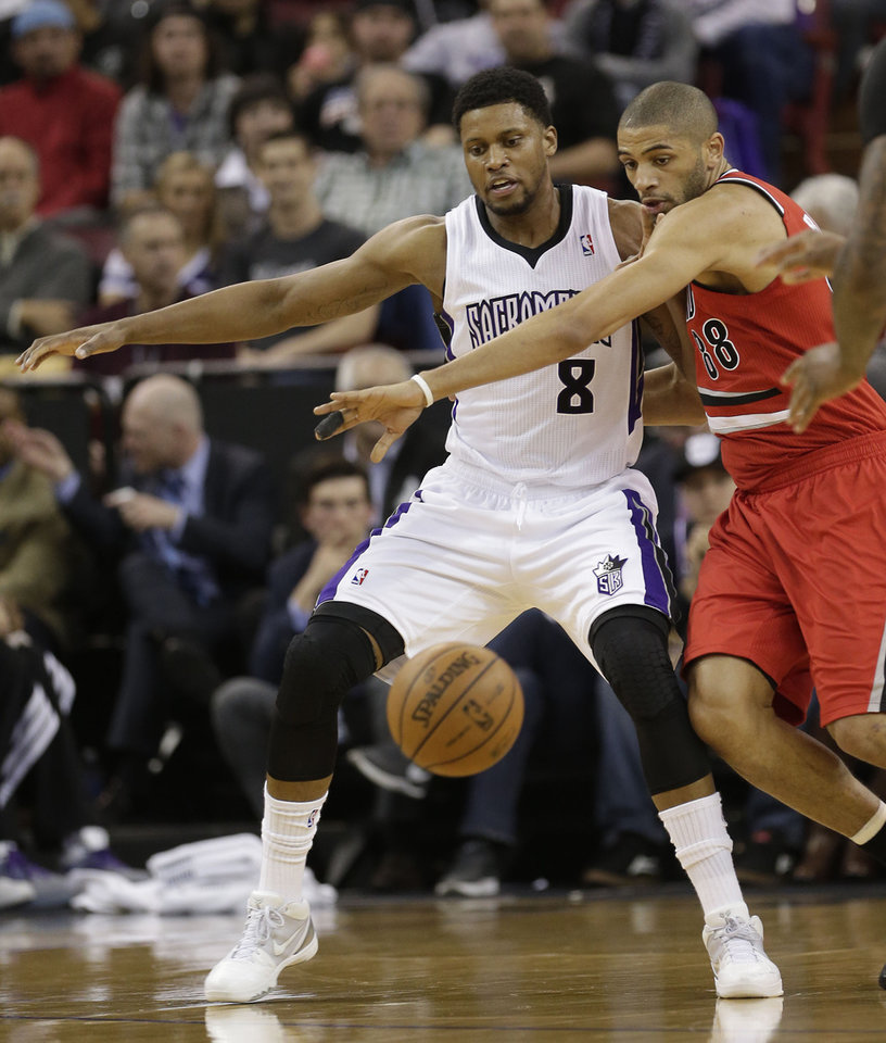 Photo - Sacramento Kings forward Rudy Gay, left, and Portland Trail Blazers forward Nicolas Batum, right, of France, battle for the ball during the first quarter of an NBA basketball game in Sacramento, Calif., Tuesday, Jan. 7, 2014. (AP Photo/Rich Pedroncelli)
