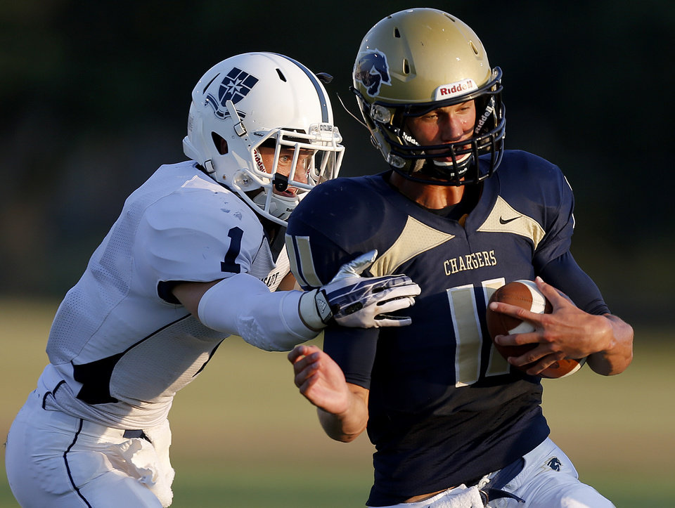 Photo - Heritage Hall's Connor McGinnis tries to get past Casady's Drew Cook during their high school football game at Heritage Hall in Oklahoma City, Thursday, September 5, 2013. Photo by Bryan Terry, The Oklahoman