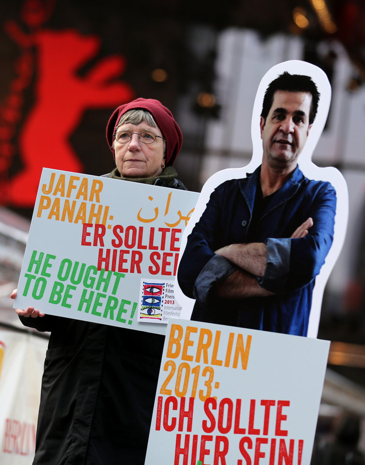 Photo - A protester shows a banner next to a portrait of Iranian director Jafar Panahi prior to the screening of the movie 'Closed Curtain' during the 63rd annual Berlin International Film Festival in Berlin, Germany, Tuesday Feb.12. 2013. The  movie from the  dissident Iranian director that defies a ban on filmmaking and reflects his frustration at being unable to work officially is making its debut at the Berlin film festival.