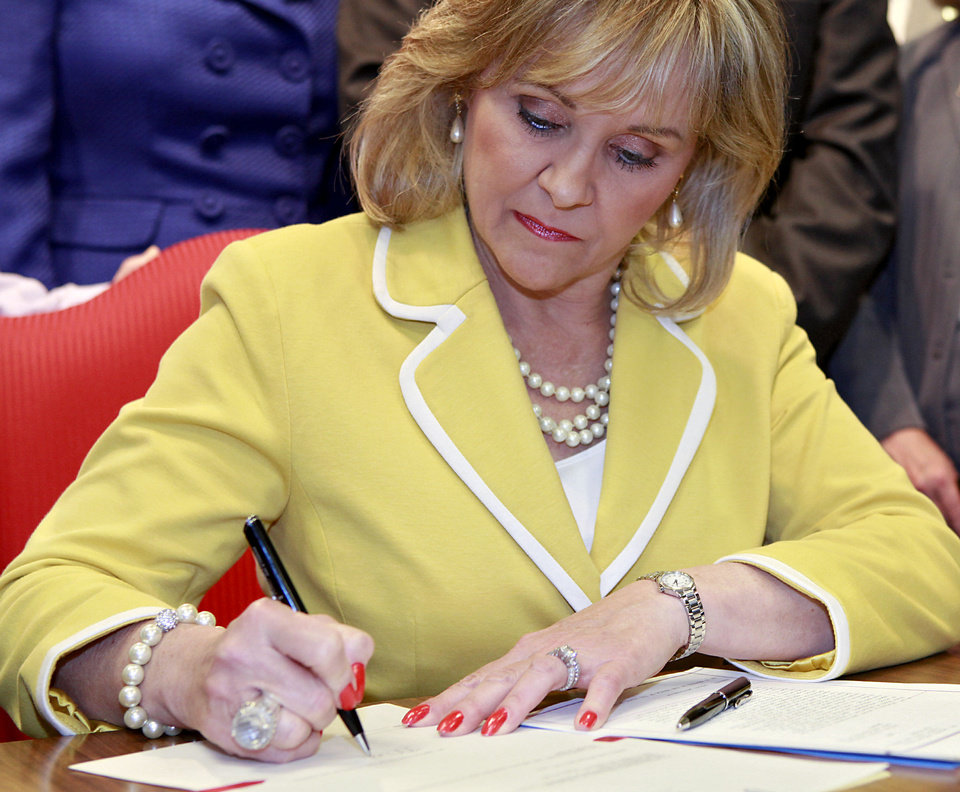 Photo - Oklahoma Governor Mary Fallin signs House Bill 1456 during a press conference at the Oklahoma state Capitol in Oklahoma City on May 4, 2011. Fallin signed two bills on Wednesday, Senate Bill 346 ends social promotion for students after the third grade and  House Bill 1456 creates an A-F system for public schools. Photo by John Clanton, The Oklahoman ORG XMIT: KOD